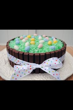 Kit Kat Easter Cake  Cake mix Icing Coconut 4 kit kat bars Mini eggs Ribbon  Put coconut shavings in a ziploc bag with 4 drops of green food coloring and shake well.