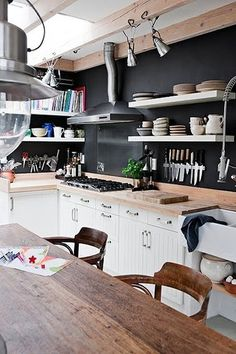 Gorgeous kitchen with black walls, light wood counters, open shelving, and cottage style cabinets.