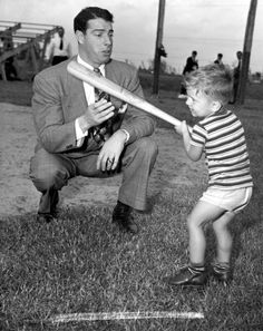New York Yankee Joe DiMaggio showing 3 year old Larry Valencourt how to hold a bat (1948). | Florida Memory