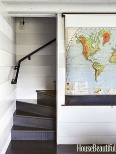 Use a vintage pull-down map to hide the television. Designed by Erin Martin and Kim Dempster. housebeautiful.com #decorating_tips #tv #living_room_ideas