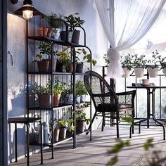 Een klein balkon met grijze stellingkast gevuld met planten, een ronde tafel en een plastic rotal stoel met armleuningen