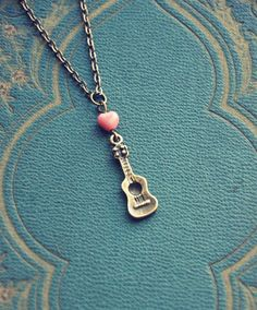 Ukulele necklace. I could repurpose the old guitar pins I have and make something like this...