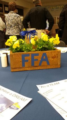 FFA centerpiece made from pallet wood, pansies, mason jars, corn and an LED tealight.