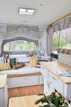A 1990s pop-up camper gets a completely new look after being remodeled with painted cabinets, new counter tops, floor, backsplash, cushion covers, ceiling, and curtains.