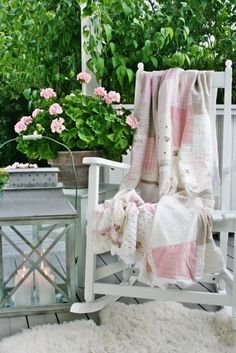 cozy corner - love the pink and white cottage look. Pale pink geranium matches the quilt.  Wonderful lantern and rocker.