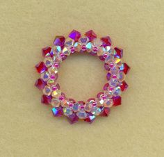 """One of my original designs named """" Circle of Hope I made this lovely pendant with 4mm Swarovski Fuscia AB2X bicones on the outer ring , 3 mm Crystal AB2X bicones on the sides and 3mm Fuscia AB2X bicones on the inside of the circle It can easily be worn on any chain as a very elegant and graceful accessory for any occasion! Approximately an inch and 1/4 in diameter. Custom orders are available upon request in your favorite colors!"""