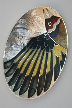 "An Elizabeth II sterling silver ""Goldfinch"" engraved and enamelled caddy spoon. Commissioned from and made by Clive Burr, enamelled by Jane Short, 2012, assayed in London. Weight: 39.7g, Size: 71mm long. (Front)"
