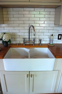 Oooh, Love the split farmhouse sink and butcher block countertop. Even digging the subway tile walls :)