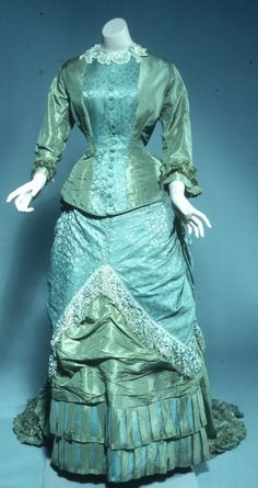 Pale blue-green silk taffeta, damask, and sateen dress with cuirasse-style bodice and chenille fringe trim, circa 1870-1880.