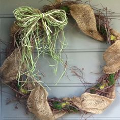 Grapevine wreath decorated with burlap, raffia, and reindeer moss.