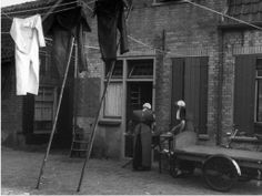 Gezicht op de voorzijde van een huis te Spakenburg (gemeente Bunschoten), met twee vrouwen in klederdracht, bezig met het strijken van kleding. 1947 WF van Heemskerck Düker (fotograaf) #Utrecht #Spakenburg