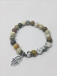 Ocean jasper can display hues and mottled accents in green, rust, grey, cream, blue, brown and caramel. The gemstone is commonly believed to promote balance of physical, intellectual and emotional bodies. It has a Mohs rating of 6.5 to 7.  The charm is known as the Hamsa Hand or the Hand of Fatima. It is a major symbol for both Jewish and Muslim faiths, but it's symbolism can be used by anyone. As the Hamsa Hand and the Hand of Fatima, the Hand is known to protect the bearer from the evil…