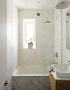 Modern Brooklyn apartment bathroom with subway tiles, bathtub, and square sink