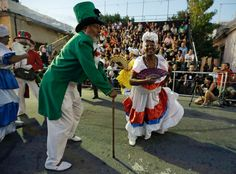 Montevideo, Uruguay Members of a comparsa (carnival group) dance during the Llamadas parade. Thousands crowd into the Barrio Sur, as costumed drummers and dancers kick off the street fiesta