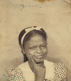 """Mozella      This is an old photograph of a young African American girl posing in a photo booth sometime during the 1930's. Written above her in faded ink is """"Mozella."""" There is nothing to indicate where this photograph was taken."""