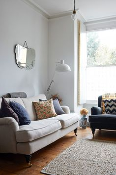 Bluebell Sofa and Chair from sofa.com layered with different colored cushions, antique etched mirror by Daniel Heath, shutters with brass piano hinges in Anna Jones London home | Remodelista