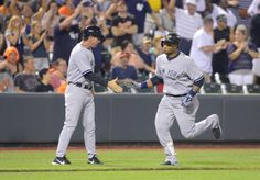 New York Yankees batter Robinson Cano is greeted by third base coach Rob Thomson after hitting the go-ahead home run off of Baltimore Oriole...
