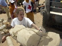 UNHCR goodwill ambassador Angelina Jolie helps Sudanese refugees load their belongings onto a truck near Tine, Chad, on June 4, 2004. The refugees are crossing the Chadian border, fleeing war-ravaged western Sudan. The actress is being honored with a Governors Award from the Academy of Motion Picture Arts & Sciences for her humanitarian contributions