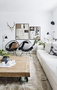 Cadeiras acapulpo pretas com almofadas estampadas, tapete felpudo, mesa de centro de madeira e obras de arte abstrata na sala de estar