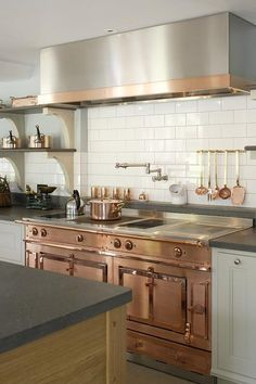 Gourmet kitchen features white cabinets paired with Italian basalt countertops situated under stacked shelves with corbels lined with copper pots and pans.