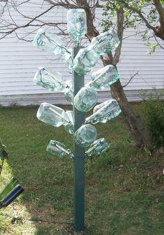 """""""Jug"""" Tree    It's six foot tall.  A gallon jug tree with 200 teal mini lights  running on a timer.  Bet this is stunning at night with the lights inside the jugs."""