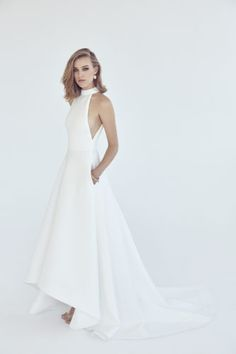 2018 Suzanne Harward Bridal - futuristic gown in neoprene with dramatic raglan cut out neckline, underarm cut out detail, pockets and circular high low skirt with train.