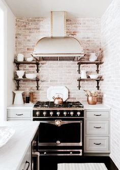 Black and white is classic. It's a simple yet bold statement that can be really be used in any room. In this kitchen, I think the stark white cabinets is offset perfectly by the black oven. The amazing distressed white brick backsplash continues the feeling of old world charm. I love the open shelves one either side of the stove. If I were to change up one things, I would rather have wide oak floors rather than black tile on the floor to echo the wooden shelves on either side of the…