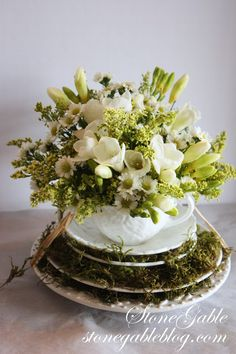 simple flowers & greenery in a teacup atop plates layered with moss