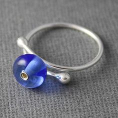 This bubbly blue beaded lampwork ring is sure to make you smile! The clear…