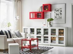 Ein weißes Wohnzimmer mit BRIMNES Schrank mit Türen in Glas/Weiß und roten Wandvitrinenschränken