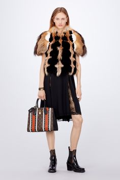 Louis Vuitton Women's Fall-Winter 2017 Collection by Nicolas Ghesquière - Look 12 This look marries one of the collection's statement fur pieces with the lingerie inspiration so prominent this season. A spectacular gilet in a blend of fox furs is worn over a light silk cocktail dress with transparent lace inserts.