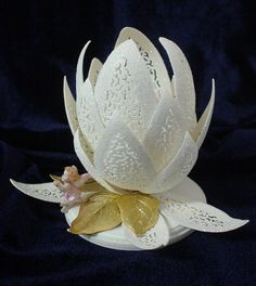 Created from pieces of goose eggs, this beautiful water lily features a tiny fairy making an offering to you.  Filigree cut with shimmery fine glitter, gold leaves and a corian base. Sold