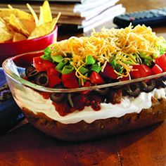 7 Layer Dip via www.culinary.net. I usually serve mine on a glass cake stand but might try it in a glass baking dish...reminds me of a trifle.