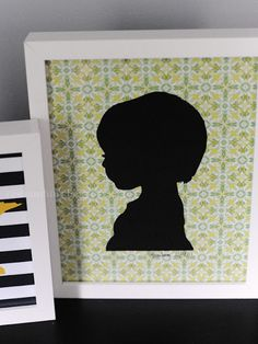 DIY silhouette- Love it! turned out adorable. I just took my kiddos pictures, put them on my computer and enlarged them all the same size, changed them to grey scale and printed them out. Then I traced over the outline and used super 77 to adhere the printouts to black cardstock. Cut out my outline and adhered them to the fancy background paper with Super 77. Insert in frame and its all done!