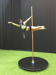 Pole dancer in Superman position, fitted with K5 wearable metabolic equipment for the measurement of oxygen consumption and other parameters.