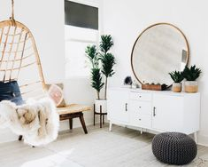 Round mirror, hanging chair, fur throw, console, knit pouf, & planter