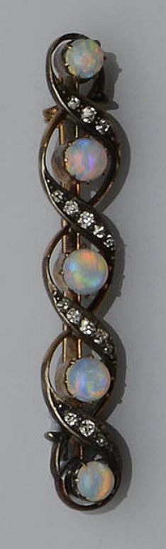 Brooch of pierced scrolling design, alternately set with circular cabochon opals and channels of graduated old-cut diamond. Victorian or Victorian style.