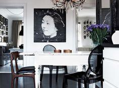 Stylowy żyrandol,biały rozkładany stół w tradycji skandynawskiej,czarne przeźroczyste krzesła z tworzywa,czarna podłoga z  żywicy i czarno-biała fotografia na ścianie (26533)