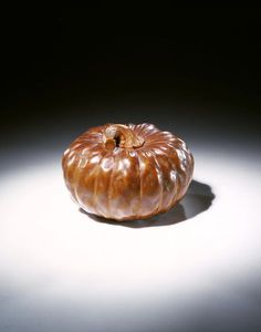 This carved and stained wood netsuke is in the form of a pumpkin by Ikkan (ca. 1850-1900)