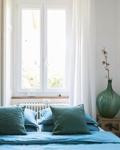 This organic modern Swiss rental apartment is filled with natural and cozy elements. The bedroom has bright blue bedding for a punch of color.