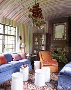 """A library in a Tuxedo Park, New York, house designed by Jeffrey Bilhuber features walls and ceilings hand-painted in candy-color stripes by decorative artist Mark Giglio; the crystal-and-wood """"dragon boat"""" light fixture is antique, the wing chair is custom-made, and the built-in bookcase is original to the Queen Anne–style home."""