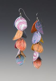 """""""Salsa Earrings""""  Silver & Paper Earrings  Created by Carol Windsor -  Multi-colored petals fall from a twig and sway on the ear. The petals are made of oxidized silver wires laminated between layers of paper many of which have been painted in shades of orange, fuchsia, and blues. The twig post is also sterling silver. Limited edition of 50. $330.00"""