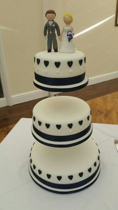 Three tier wedding cake with navy hearts. Topper couples own.