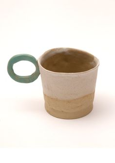A small and simple white and exposed clay cup with mint green handle.