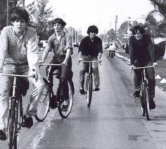 The Beatles...Paul McCartney, Ringo Starr, George Harrison and John Lennon riding bikes.