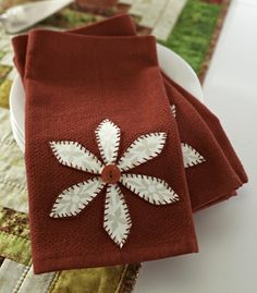 To give purchased napkins a holiday theme, at one end of each, fuse flower petals in the shape of a poinsettia and add a button to the center.