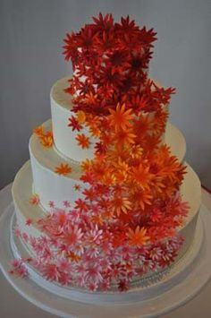 Gumpaste Daisies in a cascade of vibrant colors sweeps down the side of this traditional tiered wedding cake.