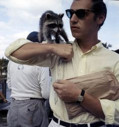 """A man with his pet raccoon on the set of the movie """"Wind Across the Everglades"""" (1958). 
