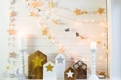 """This crafty blogger describes her mantel as """"a star studded affair."""" From beautiful wooden houses to dreamy star garlands, it's certainly putting a twinkle in our eyes.  Get the tutorial at Songbird."""