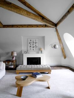 The Paris apartment of interior designer Pierre Yovanovitch features the sculptural use of wood against a smooth and uniforming coating of white.